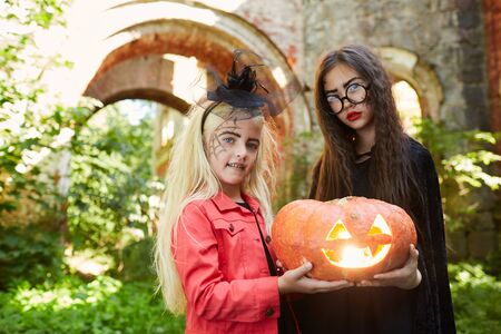 Waist up portrait of two girls wearing Halloween costumes holding carved pumpkin while posing outdoors, copy space