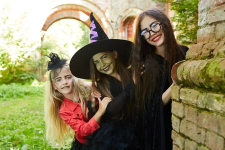 Portrait of three happy little kids going trick-o-treating on Halloween and having fun, copy space Banco de Imagens - 128448070
