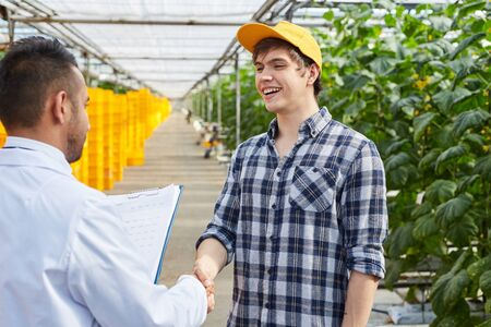 Supervisor and young grower in cap making handshake in greenhouse after concluding deal
