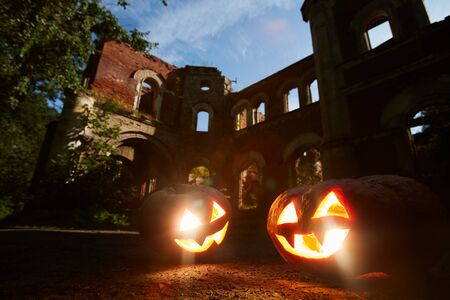 Halloween background with two carved pumpkins in front of ancient castle, copy space Stock Photo