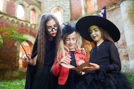 Portrait of three little witches reading magic spells outdoors