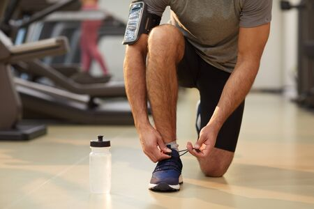 Low section portrait of unrecognizable sportsman tying shoelaces in gym, copy space