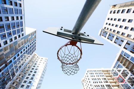 Low angle view at basketball hoop against sky in urban background, copy space