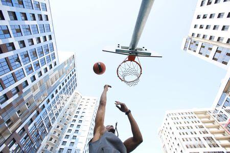 Inquadratura dal basso al giocatore di basket africano che spara slam dunk contro il cielo sullo sfondo urbano, copia spazio