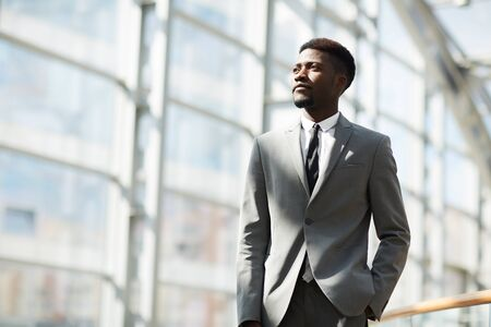 Serious pensive young Afro-American business corporation employee in gray suit holding hand in trousers pocket and looking into distance 版權商用圖片