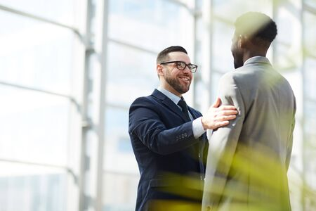 Positive bearded man in eyeglasses congratulating black colleague with career promotion and patting him on arm in lobby Banco de Imagens - 128453096