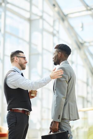 Cheerful bearded man with coffee cup patting colleague on arm while chatting with him during coffee break