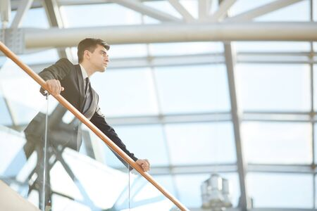 Below view of serious purposeful young male entrepreneur in suit standing at balcony in lobby and looking into distance