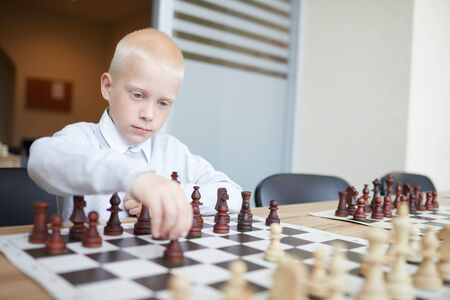 Blonde schoolboy in white shirt making first chess move in game with imaginary opponent