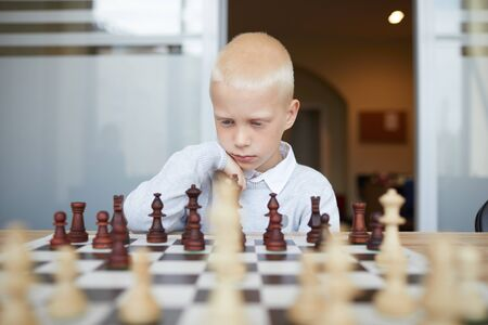 Thoughtful schoolboy playing chess, carefully thinking about his next move and analyzing strategy of opponent Stock Photo