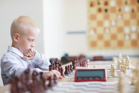 Blonde schoolboy in white shirt seriously thinking about chess game with imaginary opponent