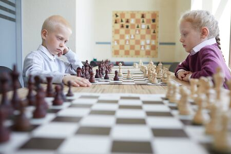 Blonde boy and girl with braided red hair playing chess at table in classroom of chess club