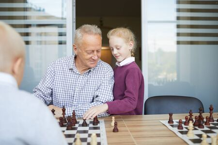 Small girl with red braided hair helping her grandfather to win chess game against her brother