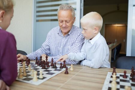 Blonde schoolboy suggesting his grandfather chess move in chess game against his younger sister