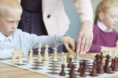 Boy in white shirt and girl in purple sweater learning to play chess in chess class at school