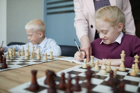 Smiling schoolgirl in purple sweater writing down chess rules while teacher pointing at notebook