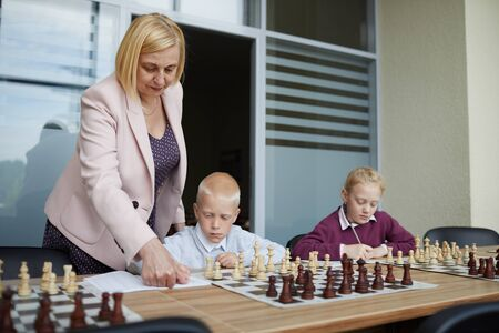 Blonde female teacher showing chess rules at notebook where schoolboy writing them down Фото со стока