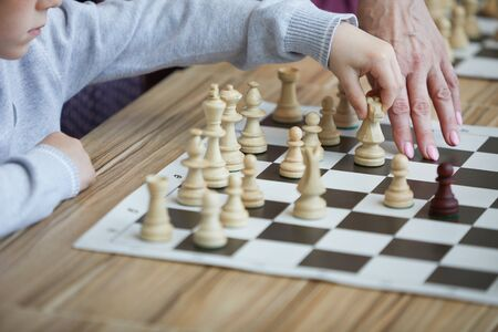 Hand of teacher showing boy in gray sweater chess move on chess board which can help to win