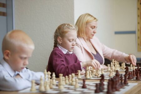 Two schoolchildren and teacher practicing chess combinations during lesson in chess club Фото со стока - 128453565