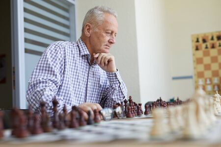 Old man in checked shirt playing chess with imaginary opponent in chess classroom at school Stock Photo