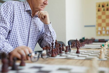 Old man in checked shirt holding glasses and thinking about next chess move in game with imaginary opponent