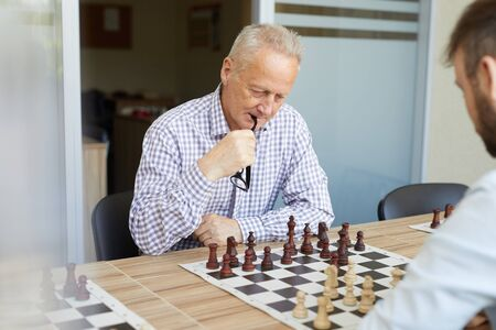 Focused old man in checked shirt biting his glasses while playing chess with his young son Фото со стока