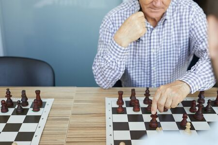 Concentrated old man in checked shirt making deliberate chess move in game during chess tournament