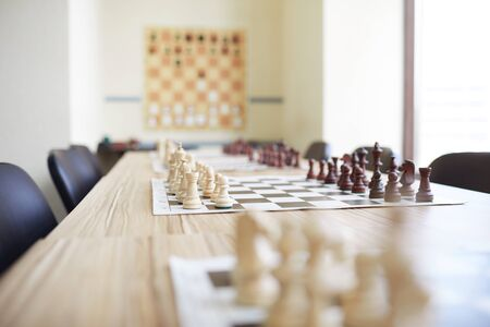 Long beige table covered with chess boards and surrounded by chairs in chess classroom at school