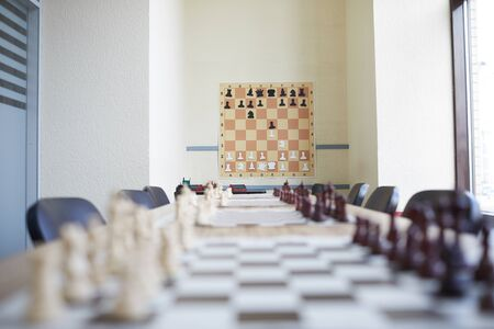 Chess classroom at school with chess poster on wall and long table with various chess boards