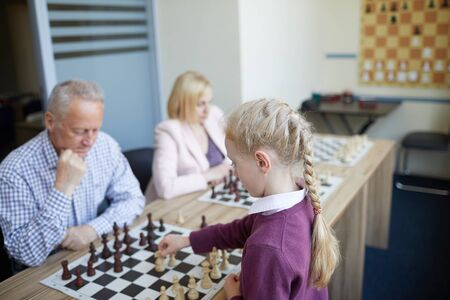 Intense chess game where adult experienced sportsman playing with school girl with braided hair Stock Photo