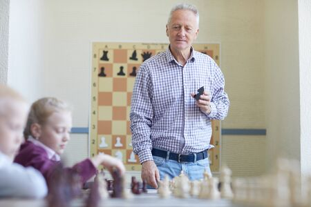 Aged male teacher showing chess figure and explaining chess moves for two schoolchildren Фото со стока