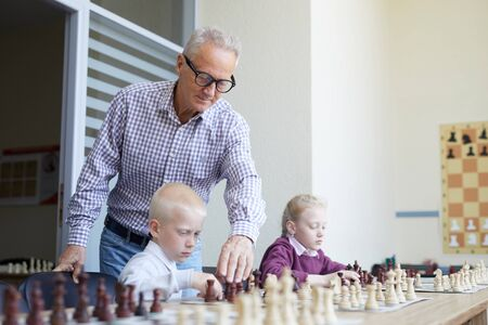 Aged male teacher with glasses helping two schoolchildren with learning chess combinations during chess class Фото со стока - 128453616