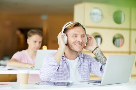 Positive excited handsome young guy with tattoo sitting at desk in library and adjusting headphones while preparing to work on project