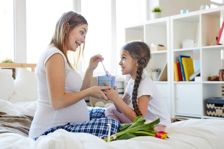 Full length portrait of cute little girl giving present to mom on Mothers day, both sitting on comfortable bed in morning, copy space Imagens