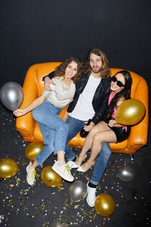 Directly above view of satisfied handsome hipster young man with long hair sitting on sofa with cool girls and embracing them while drinking alcohol from bottle.