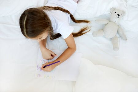 Above view portrait of cute little girl drawing handmade card for Mothers day while laying in bed on white sheets, copy space