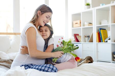 Full length portrait of cute little girl embracing pregnant mother and giving her flowers on Mothers day, both sitting on comfortable bed in morning, copy space
