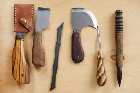 Top view background image of leatherworking tools lying on wooden table, copy space