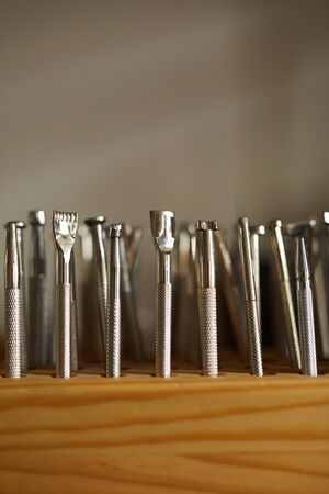 Extreme close up of leatherworking tools on stand in atelier workshop, copy space