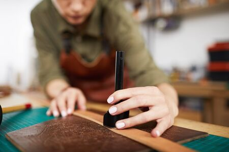 Closeup of unrecognizable artisan working with leather in small shop, copy space Stock fotó