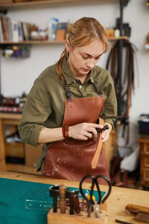 Warm toned waist up portrait of female craftsman working with leather in tannery shop, copy space Stock fotó