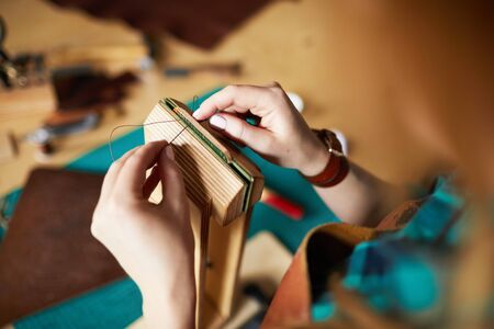 Close up of female hands sewing leather bag in leatherworking shop, copy space