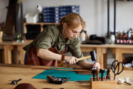 Portrait of woman artisan making leather belt in shop lit by sunlight, copy space Stock fotó