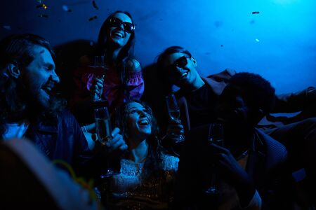Group of positive young friends laughing together and drinking champagne in dark room with blue light, girl excited about falling confetti