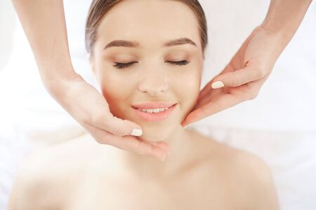 Above view portrait of beautiful young woman enjoying face and neck massage in SPA , closeup