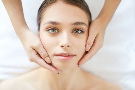 portrait of beautiful young woman looking at camera while enjoying head massage in Spa Stock Photo