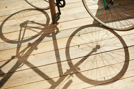 Above view background of bicycle shadow over wooden floor in sunlight, copy space