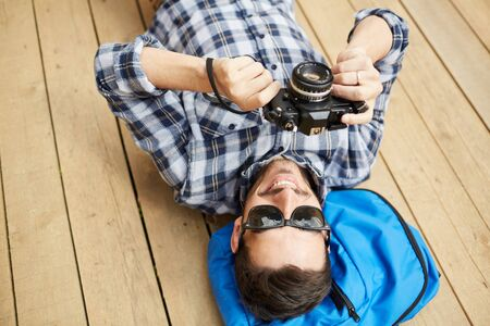 Above view portrait of young tourist taking photos while lying on wooden floor, copy space