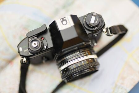 Above view background of retro photo camera over map, tourism and travel concept, copy space