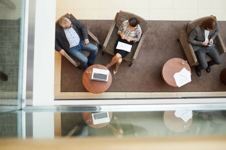 Above view background of waiting room or office lobby with people siting in comfortable chairs enjoying relaxing working space, copy space Stockfoto